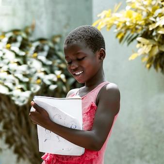 Criança com tiro médio segurando caderno