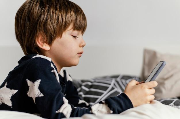 Criança com tiro médio segurando o telefone