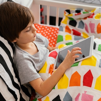 Criança com tiro médio segurando tablet