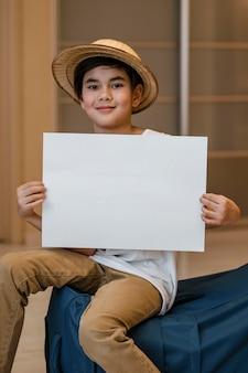 Criança com tiro médio segurando um pedaço de papel