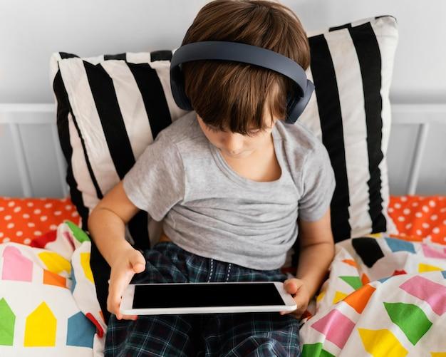Criança com tiro médio usando fones de ouvido