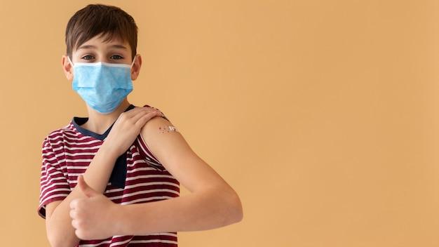 Criança com tiro médio usando máscara facial