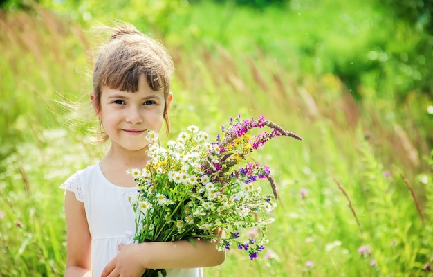 Criança com um buquê de flores silvestres. foco seletivo. natureza.