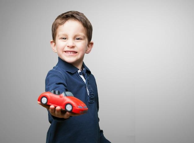 Criança com um carro vermelho