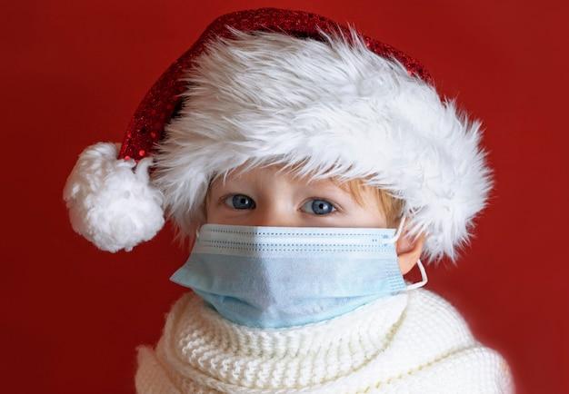 Criança com um chapéu de papai noel vermelho está doente no natal, é protegida contra vírus por uma máscara médica