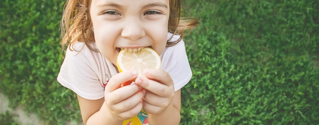 Criança com um limão. foto. comida e bebida.