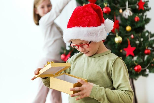 Criança com um presente dourado e um chapéu de santa