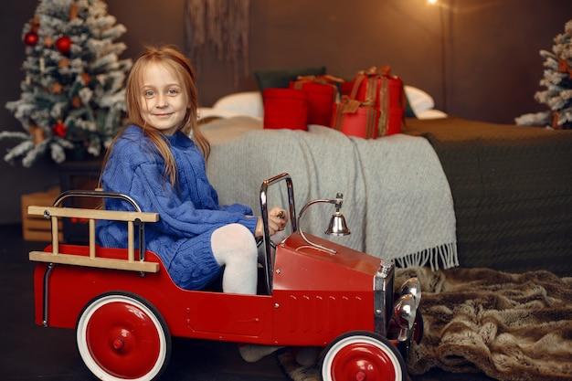 Criança com um suéter azul. filha sentada perto da árvore de natal.