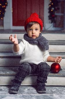 Criança com um suéter branco e um chapéu de malha vermelho sentada na escada com neve em casa no natal