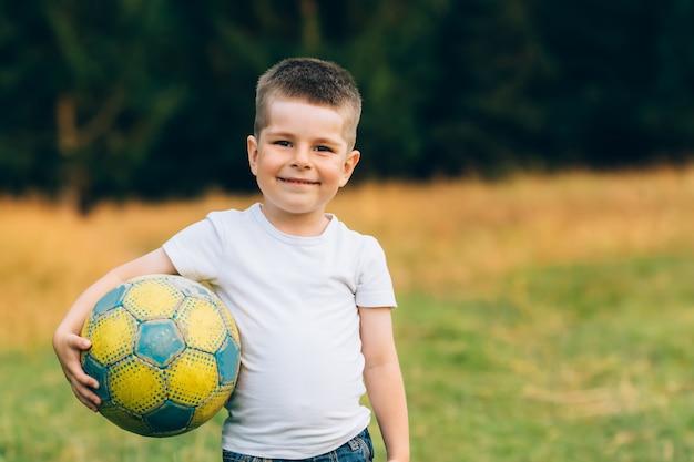 Criança com uma bola de futebol debaixo do braço no jardim de casa com fundo de grama, sorrindo