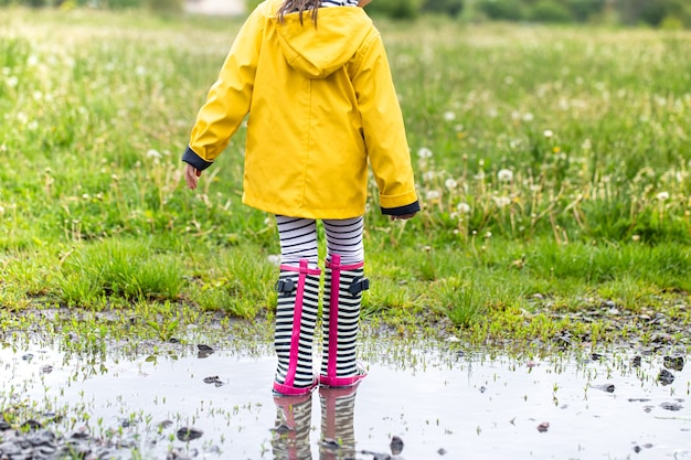Criança com uma capa de chuva amarela brilhante e botas de borracha listradas.