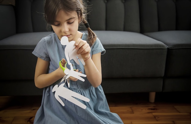 Criança com uma família de papel nas mãos.