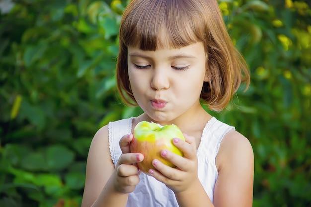 Criança com uma maçã. foco seletivo. natureza