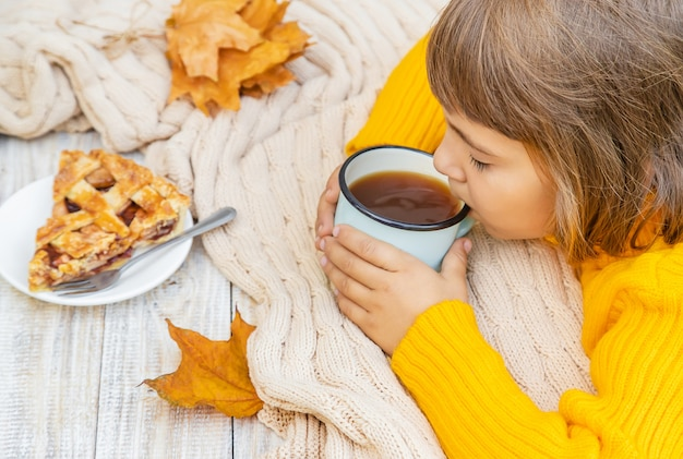 Criança com uma xícara de chá nas mãos dele.