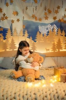 Criança com ursinho de pelúcia na atmosfera de natal