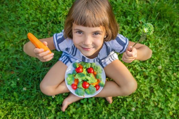 Criança come legumes, brócolis e cenoura
