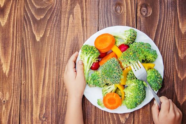 Criança come legumes. foto de verão. foco seletivo.