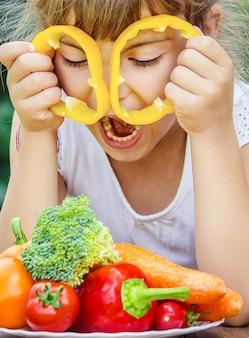 Criança come legumes. foto de verão. foco seletivo