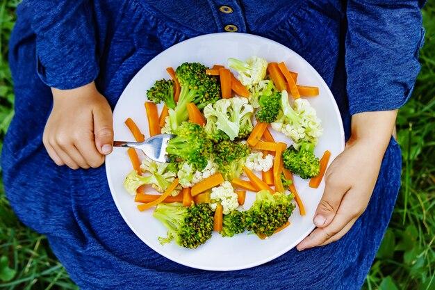 Criança come legumes