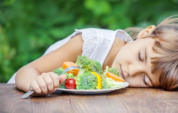 Criança come legumes.