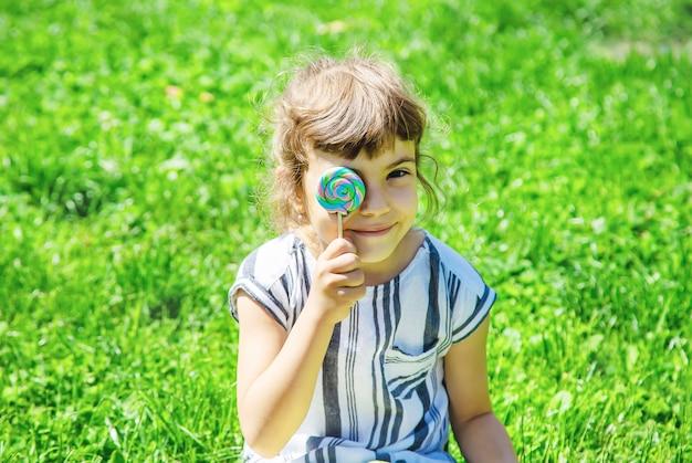 Criança come pirulito na natureza. foco seletivo.