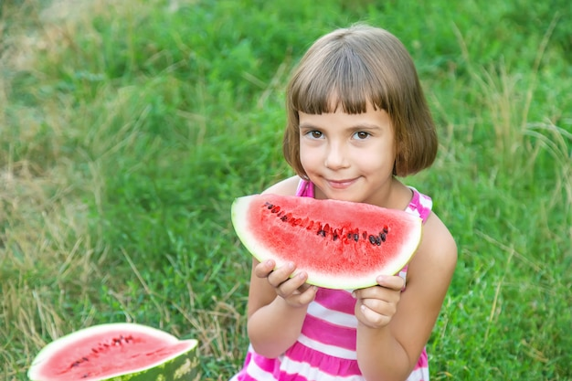 Criança come uma melancia no jardim