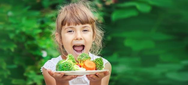 Criança come vegetais