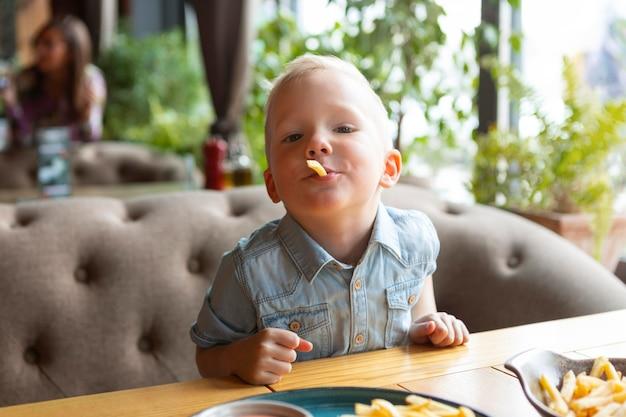 Criança comendo batata frita em restaurante