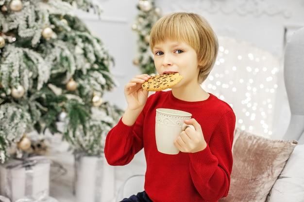 Criança comendo biscoitos de natal e bebendo leite.