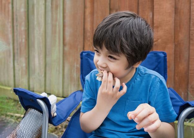 Criança comendo bolinho de hambúrguer no jardim