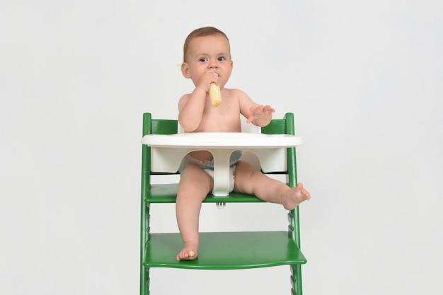 Criança comendo e sentada em uma cadeira alta no fundo branco
