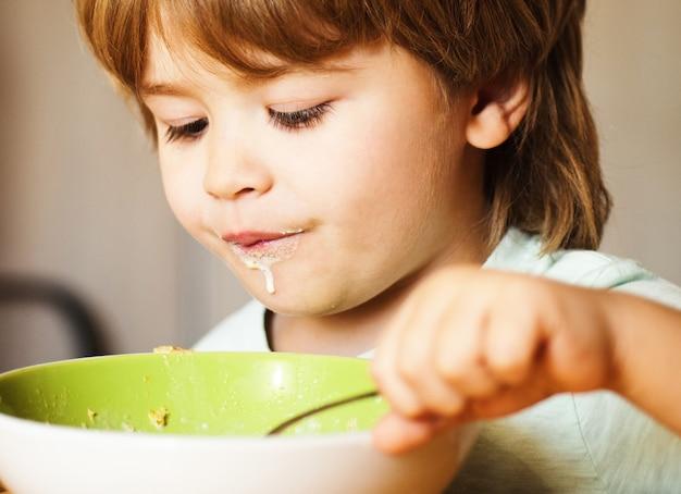 Criança comendo. garotinho tomando café da manhã na cozinha