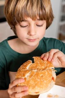 Criança comendo hambúrguer em casa