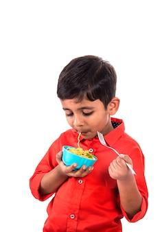 Criança comendo macarrão delicioso, criança indiana comendo macarrão com garfo