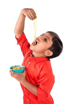 Criança comendo macarrão delicioso, garoto indiano comendo macarrão com garfo na parede branca
