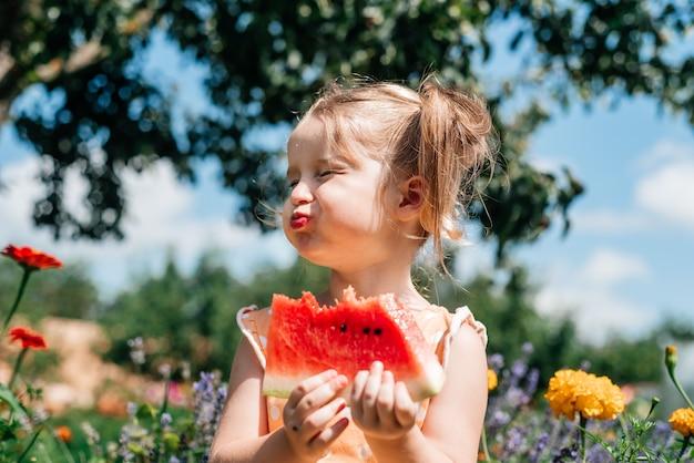 Criança comendo melancia no jardim. as crianças comem frutas ao ar livre. lanche saudável