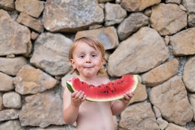 Criança comendo melancia no jardim durante as férias de verão. as crianças comem frutas ao ar livre. lanche saudável para crianças. garotinho, degustando uma fatia de melancia.