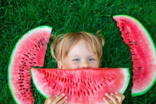 Criança comendo melancia no parque no horário de verão