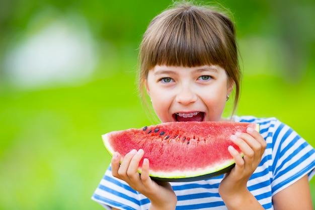 Criança comendo melancia pré adolescente menina no jardim segurando uma fatia de melancia menina feliz criança e ...