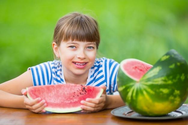 Criança comendo melanciapre menina adolescente no jardim segurando uma fatia de melancia menina feliz criança comer ...