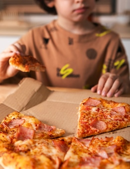 Criança comendo pizza em casa