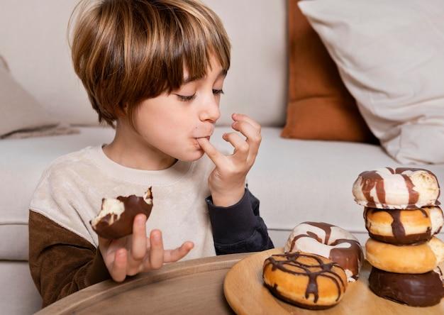 Criança comendo rosquinhas em casa