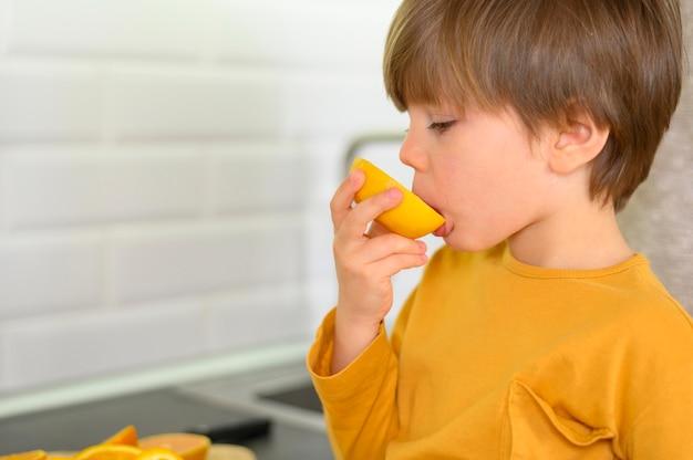 Criança comendo uma laranja na cozinha
