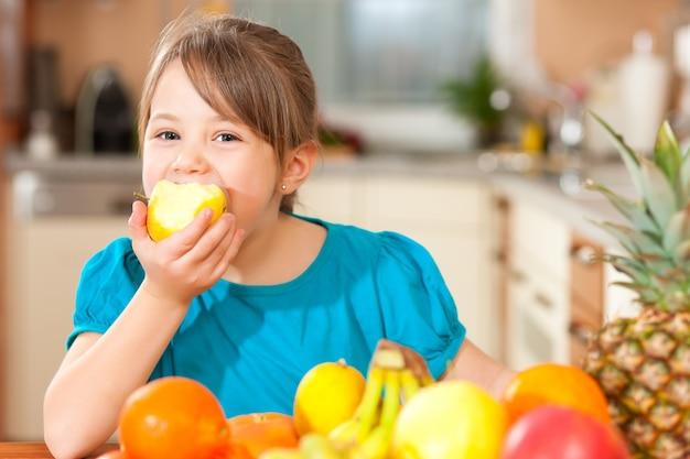 Criança comendo uma maçã
