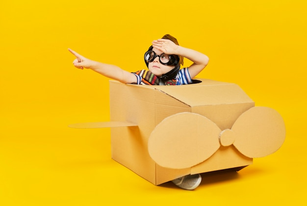 Criança como astronauta em um avião de brinquedo apontando