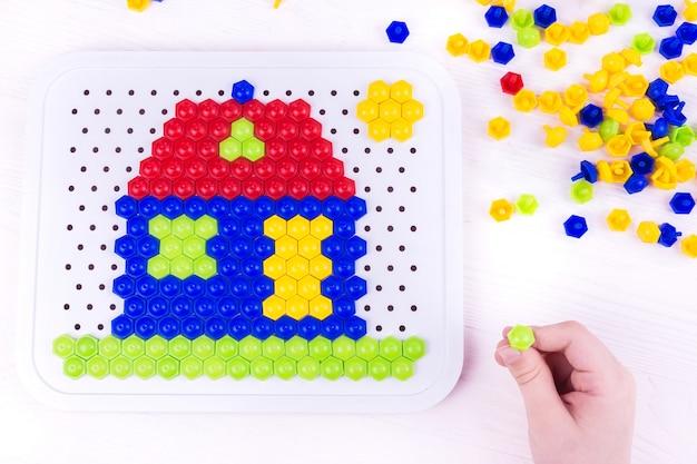 Criança construindo uma casa de mosaico