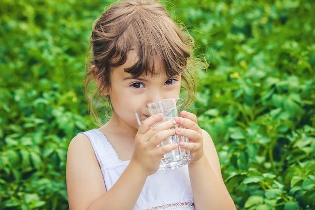Criança copo de água. foco seletivo.