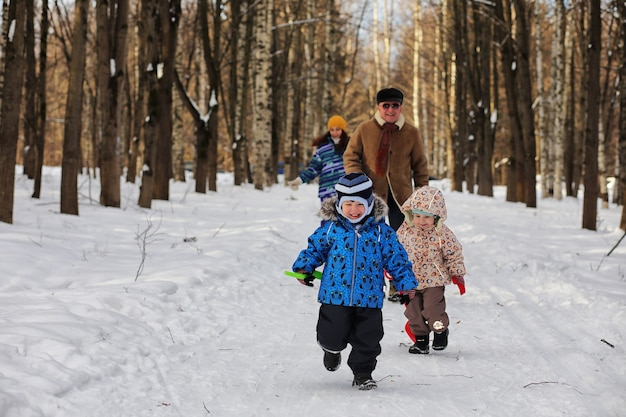 Criança correndo em um parque de inverno e se divertindo com a família