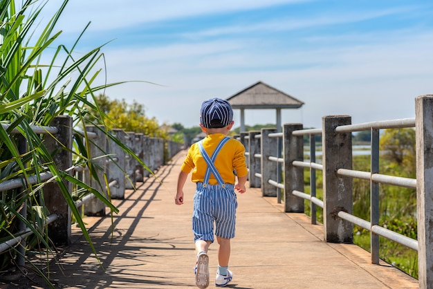 Criança correndo na ponte na natureza.
