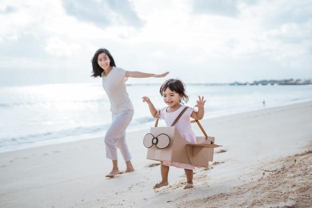 Criança correndo na praia brincando com um aviãozinho de papelão com a mãe